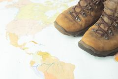 A pair of brown, worn suits against a geographical map. Selective focus. Concept of travel and adventure. Horizontal frame royalty free stock image