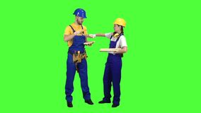 Pair of builders choose wooden boards. Green screen. Slow motion. Pair of builders choose wooden boards and communicate among themselves on different topics stock footage