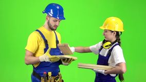 Pair of builders choose wooden boards. Green screen. Slow motion. Pair of builders choose wooden boards and communicate among themselves on different topics stock video