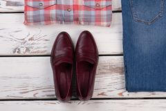 Pair of burgundy shoes. Western style combination of plaid shirt, blue denim and leather footwear. Folded clothes Royalty Free Stock Photos