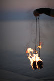 Pair of burning poi in fire dancer hand. Spinning poi in flame on dark sea background Stock Photos