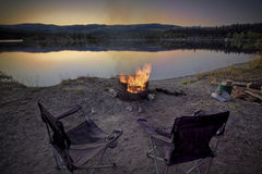 Pair of Camper Chairs. A pair of camp chairs near the campfire on a still mountain lake at dusk Stock Images
