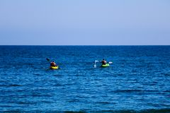 A pair of canoes in the Pacific. People kayak in the ocean royalty free stock photo