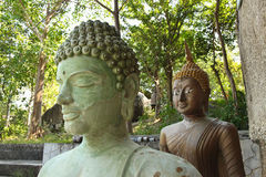 Pair of Carved Stone Buddha Statues. A pair of carved stone Buddha statues stand at a forest mountain temple monastery in Thailand, Southeast Asia, along the Royalty Free Stock Photography