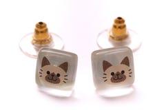 A pair of cat face earrings Stock Photos