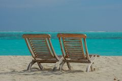Pair of chairs on the beautiful beach at the tropical island at resort. At Maldives Royalty Free Stock Image