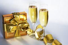 Pair of champagne flutes. And golden gift box royalty free stock images
