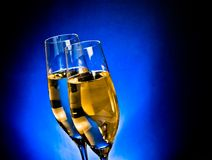 A pair of champagne flutes on dark blue light background Royalty Free Stock Photo
