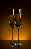 A pair of champagne flutes on dark golden light background Stock Photo