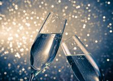 A pair of champagne flutes with golden bubbles on blue light bokeh background Royalty Free Stock Images