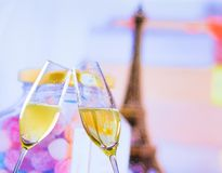 A pair of champagne flutes with golden bubbles on blur tower Eiffel background. A pair of champagne flutes with golden bubbles make cheers on blur tower Eiffel Stock Photos