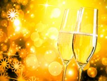 A pair of champagne flutes with golden bubbles on golden light background Stock Photo