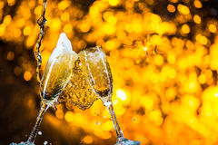 A pair of champagne flutes with golden bubbles make cheers on golden light background with space for text Stock Image