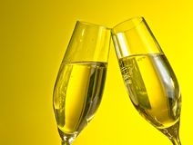 A pair of champagne flutes with golden bubbles on yellow light background Stock Image