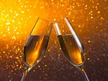 Pair of a champagne flutes on golden light bokeh background Royalty Free Stock Photo