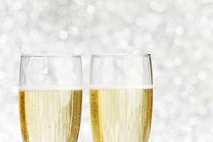 Pair of champagne flutes. On shiny glitter background Stock Photography