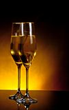 A pair of champagne flutes on table on dark golden light background Stock Photos