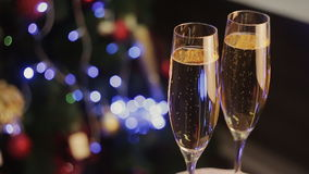 Pair of champagne glasses, Christmas tree ornament as the background. Champagne in two glasses  the christmas background stock footage