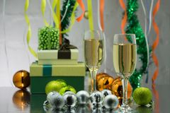 Pair of champagne glasses and sparkler, Christmas tree ornament as the background.  Stock Photos