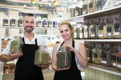 Pair of charming sellers with aprons at store of herbs and ecological food. Portrait of pair of charming sellers with aprons at store of herbs and ecological stock photos