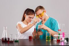 A pair of chemists add a red liquid from the measuring pipette to a flask with a dark liquid in a transparent flask. royalty free stock photography
