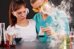 A pair of chemists, a guy and a girl, stand in smoke and examine a transparent flask with a green liquid. royalty free stock photography