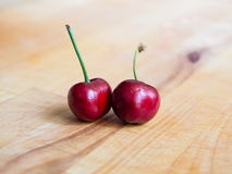 Pair of cherries on a plank. Pair of sweet cherries on a plank Royalty Free Stock Photography