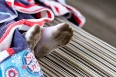 Pair of child feet in dirty stained white socks. Kid soiled socks while playing outdoors. Children clothes bleaching and washing t royalty free stock photo