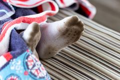 Pair of child feet in dirty stained white socks. Kid soiled socks while playing outdoors. Children clothes bleaching and royalty free stock photo