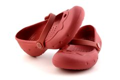 Pair of child red rubber shoes. On white background stock photos