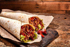 Pair of Chili Stuffed Tex Mex Wraps on Wood Table. Close Up Still Life of Pair of Chili Stuffed Tex Mex Fajita Wraps Wrapped in Grilled Flour Tortillas and royalty free stock photos