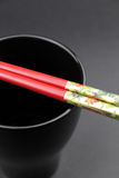 Pair of Chinese chop sticks on a black cup Stock Photography