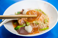 A pair of chopsticks holding a squid with a bowl of Thai Noodle Royalty Free Stock Photo