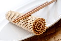 A pair of chopsticks and a sushi mat Royalty Free Stock Images