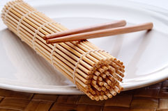 A pair of chopsticks and a sushi rolling mat Stock Photos