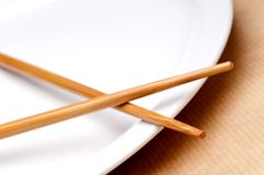 A pair of chopsticks on a white pla Royalty Free Stock Photos