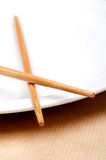 A pair of chopsticks on a white plate Royalty Free Stock Images