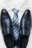 Pair of classic blue shoes standing on a shirt and tie. Men`s fashion. View from above Stock Photography