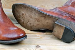 Pair of classic leather brown cowboy boots. Pair of new classic leather brown cowboy boots on wooden boards. Macro shooting stock photography