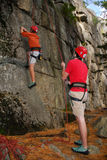 Pair of Climbers. Two climbing partners in red shirts work a rope and make the way up the rock face Stock Image
