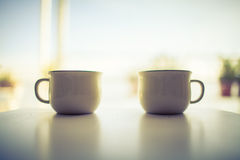 A Pair of Coffee Cups. Two coffee cups on the  white wooden table Royalty Free Stock Photography