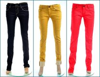 Pair of colored jeans, isolated. Colored denim jeans in black, yellow and red royalty free stock photo