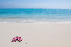 Pair of colored sandals on a white sand beach Royalty Free Stock Image