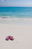 Pair of colored sandals on a white sand beach Stock Photos