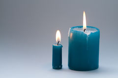 Pair colorful greenish-blue, turquoise candles on gradient gray background. Two pieces. each candle with natural flame Stock Photos