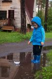 Pair of colorful rubber boots in a big puddle. Boy having fun after rain. Outdoor. Pair of colorful rubber boots in a big puddle. Boy having fun after rain royalty free stock image