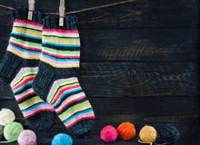 Pair of colorful striped woolen socks. Hanging on clothesline on dark wooden vintage background with multicolored balls of yarn and room for copy space Royalty Free Stock Image