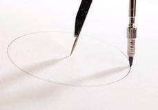 Pair of compasses drawing circle Stock Photo