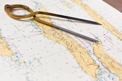Pair of compasses for navigation on a sea map. With low depth of field Stock Images