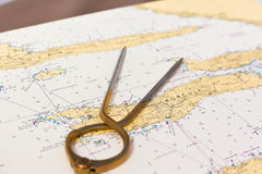Pair of compasses for navigation on a sea map. With low depth of field Stock Photos